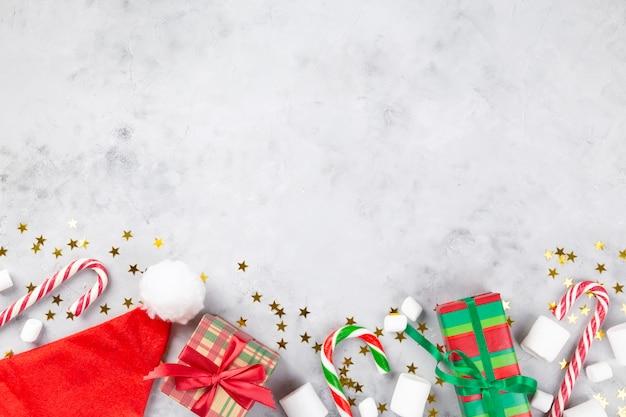 Composición navideña. regalos, bastón de caramelo, marshmellow, gorro de papá noel sobre fondo de hormigón gris con estrellas brillantes