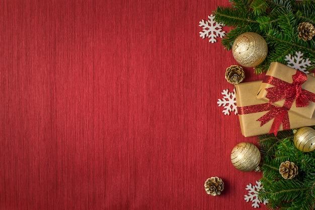 Composición navideña con regalos, bolas doradas, piñas, ramas de abeto y copos de nieve sobre un fondo rojo.