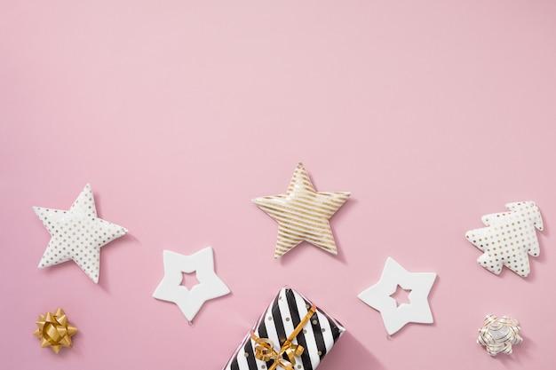 Composición navideña. regalos de navidad, decoraciones negras y doradas sobre fondo rosa pastel.