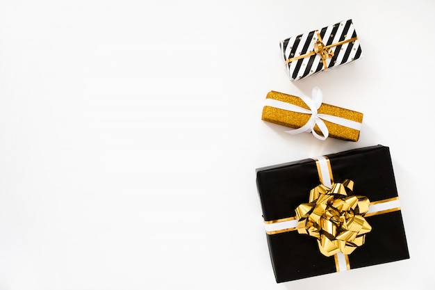 Composición navideña. regalos de navidad, papel de regalo negro y dorado sobre fondo blanco.