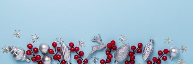 Composición navideña con regalos plateados y bayas de acebo