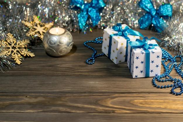 Composición navideña con regalos, velas y copos de nieve decorativos sobre fondo de madera