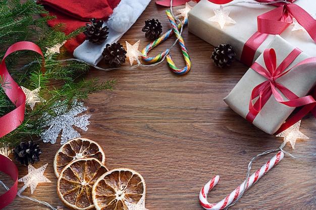 Composición navideña sobre un fondo de madera oscura con una rama de abeto, regalos, dulces y una guirnalda.