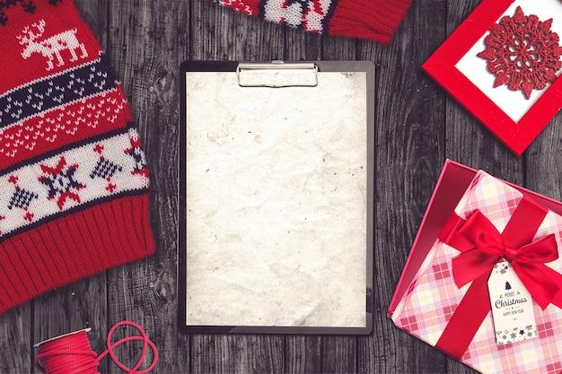 Composición navideña con suéter, portapapeles y regalos