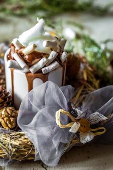 Composición navideña taza de cacao con malvaviscos, sobre madera