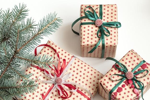 Composición navideña de varias cajas de regalo envueltas en papel artesanal y decoradas con cintas de raso. vista superior, endecha plana. pared blanca.