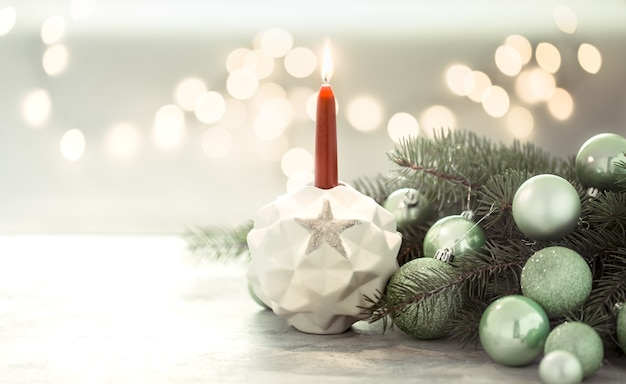 Composición navideña con una vela en un candelero y bolas navideñas