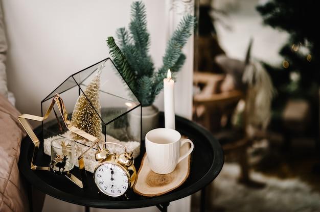 Composición navideña. vela, taza de café, reloj de oro vintage, portavelas de metal dorado en forma de estrella sobre la mesa. interiorismo y decoración a domicilio. de cerca. nochebuena.