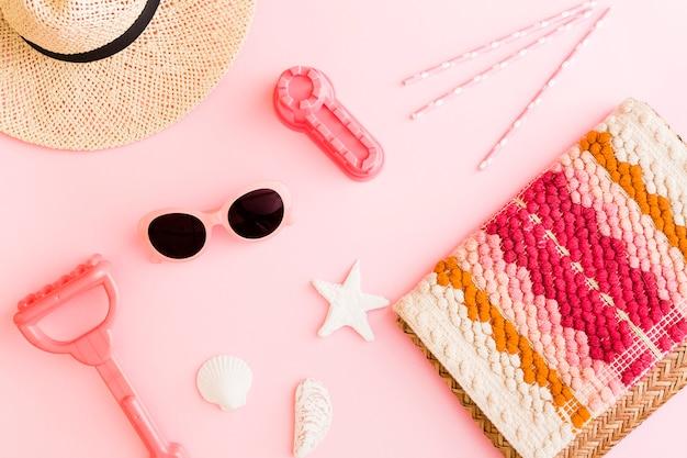 Composición con objetos de playa sobre fondo rosa