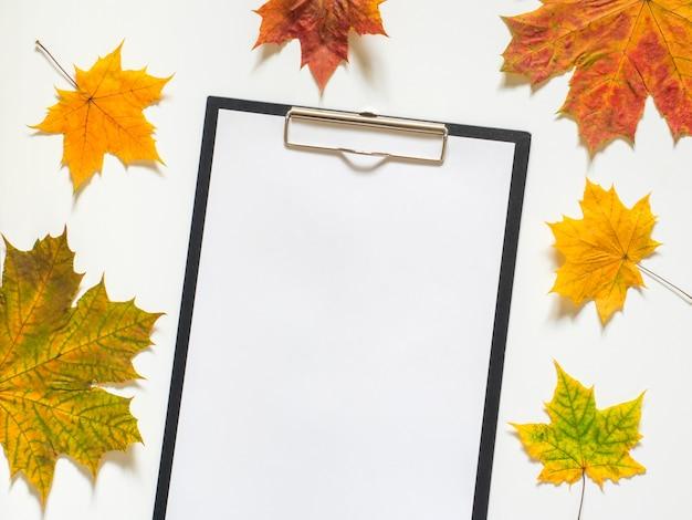 Composición otoñal de hojas de arce amarillas y papel en blanco sobre fondo blanco.