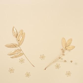 Composición otoñal con hojas otoñales de serbal en color dorado sobre una superficie beige neutra