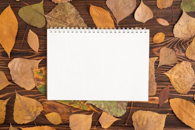 Composición de otoño con bloc de bocetos en blanco