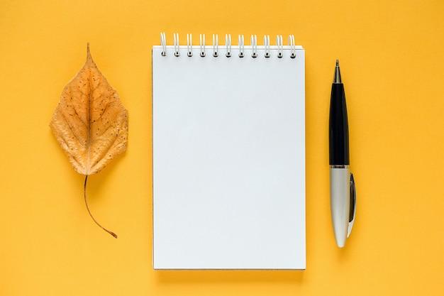Composición de otoño. bloc de notas en blanco blanco, hoja de naranja seca y pluma en amarillo.
