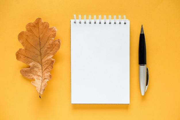 Composición de otoño. bloc de notas en blanco blanco, hoja de roble naranja seca y bolígrafo sobre amarillo