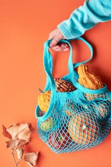 Composición de otoño: bolsa de hilo turquesa con calabazas y mano femenina en suéter azul sobre papel naranja