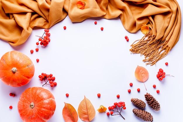 Composición de otoño con bufanda amarilla, hojas, bayas rojas sobre fondo pastel