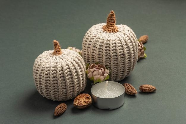 Composición de otoño con calabazas de ganchillo, velas, especias y decoración tradicional. un moderno fondo gris oscuro, de cerca