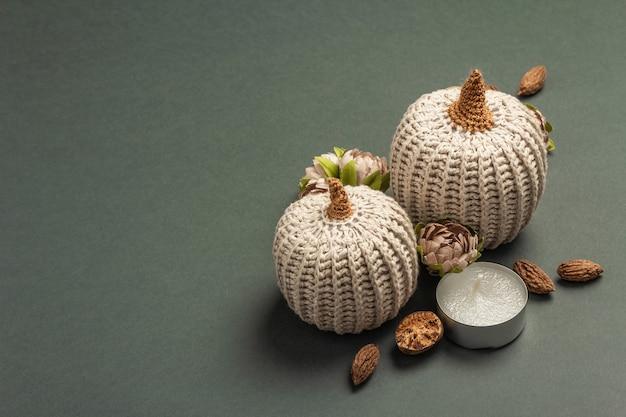 Composición de otoño con calabazas de ganchillo, velas, especias y decoración tradicional. un moderno fondo gris oscuro, lugar para texto
