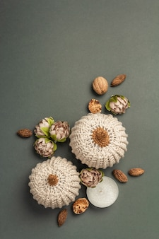 Composición de otoño con calabazas de ganchillo, velas, especias y decoración tradicional. un moderno fondo gris oscuro, vista superior