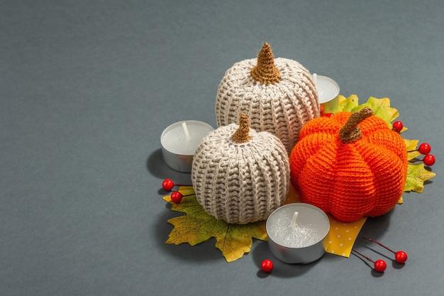 Composición de otoño con calabazas de ganchillo, velas, hojas y decoración tradicional. luz dura de moda, sombra oscura. fondo gris mate, espacio de copia