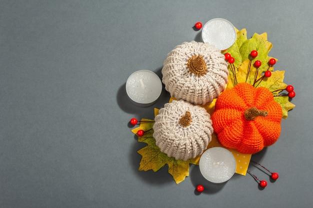 Composición de otoño con calabazas de ganchillo, velas, hojas y decoración tradicional. luz dura de moda, sombra oscura. fondo gris mate, vista superior