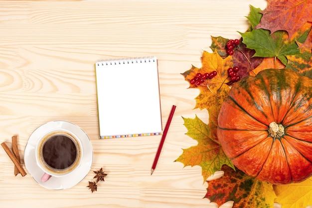 Composición de otoño. cuaderno con bolígrafo, café caliente, calabaza, hojas sobre fondo blanco de madera