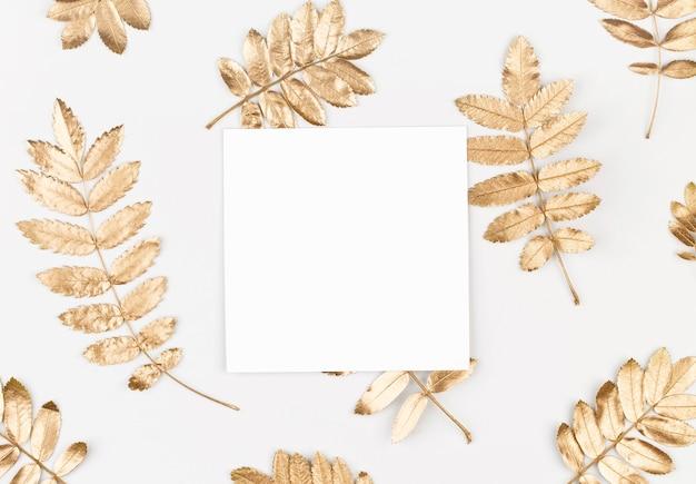 Composición de otoño hojas doradas de otoño sobre fondo blanco con una tarjeta en blanco de papel blanco lay flat