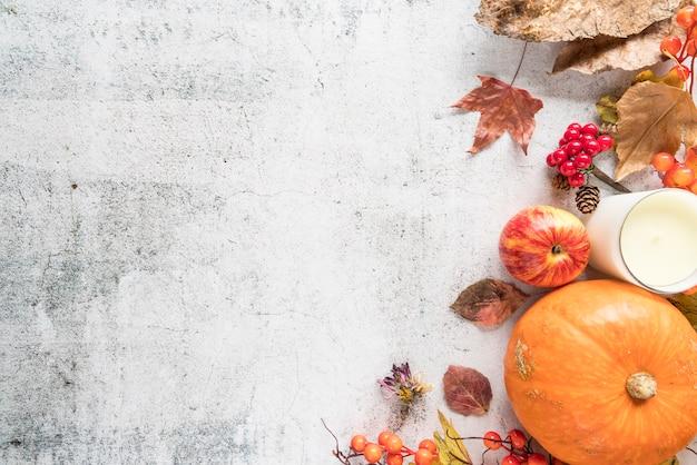 Composición de otoño con hojas en superficie ligera.