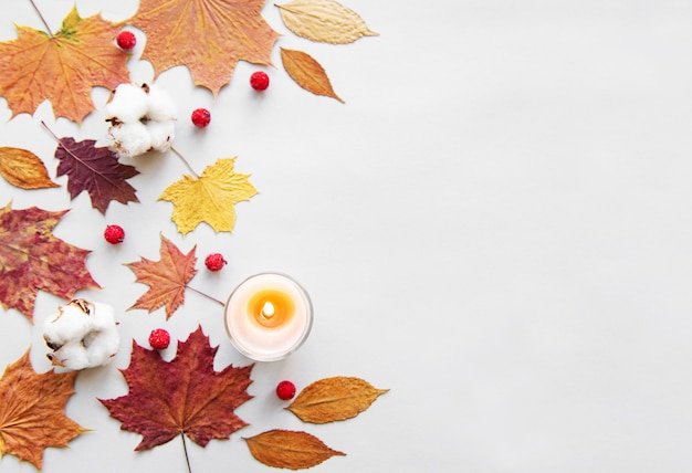 Composición de otoño con hojas y velas sobre fondo blanco.