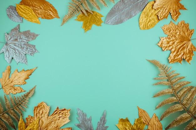 Composición de otoño con marco de hojas doradas en menta