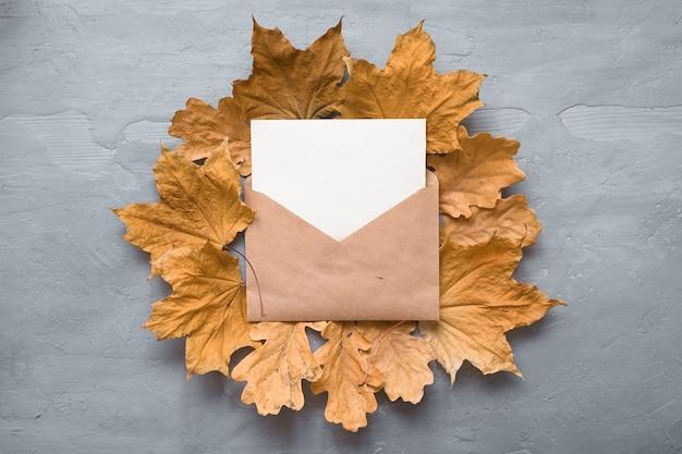 Composición de otoño. sobre artesanal. tarjeta en blanco con hojas de arce otoñal. lay flat, vista superior, espacio de copia.