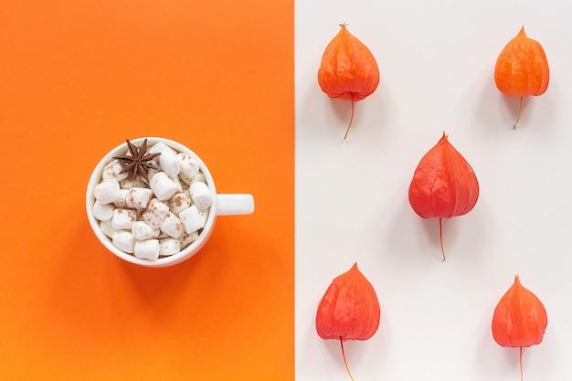 Composición de otoño taza de cacao con malvaviscos y flores rojas secas de otoño