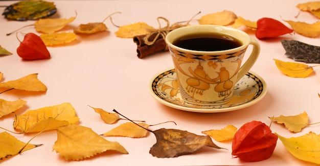 Composición de otoño con taza de café y bastón de canela bastidor de hojas de otoño