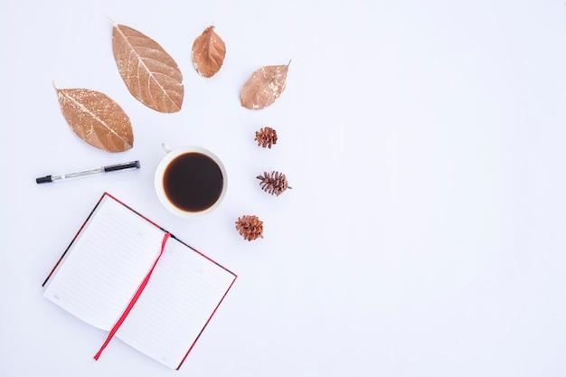 Composición de otoño. taza de café, hojas secas, libro y bolígrafo sobre fondo blanco. otoño, concepto de otoño. endecha plana, vista superior, espacio de copia