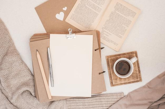Composición de otoño taza de café, libro, manta, cuaderno, suéter de moda femenina.
