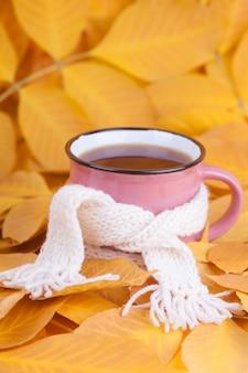 Composición de otoño taza de té envuelta en una bufanda té matutino de temporada