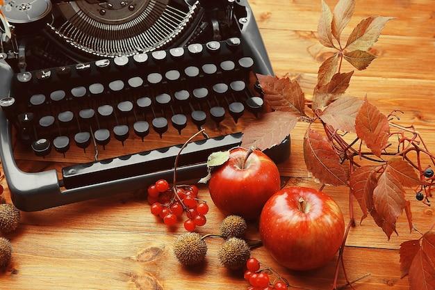 Composición de otoño con vieja máquina de escribir sobre mesa de madera