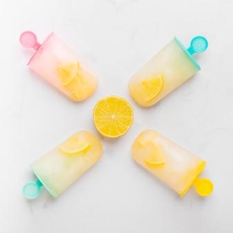 Composición de paletas cortadas de limón y hielo con cítricos en palitos de colores