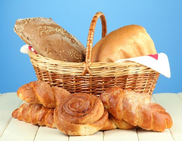 Composición con pan y bollos, en canasta de mimbre sobre mesa de madera en azul