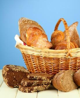 Composición con pan y bollos, en canasta de mimbre sobre mesa de madera, sobre superficie de color