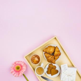 Composición de la panadería, taza y presente con etiqueta en la bandeja cerca de la flor