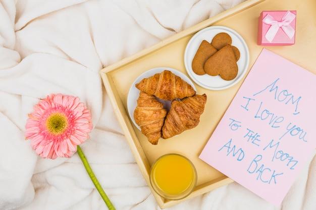 Composición de panadería, vidrio y papel con palabras en la bandeja cerca de la flor