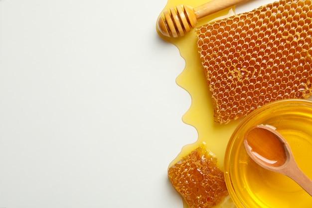 Composición con panales, miel y cucharón sobre fondo blanco.