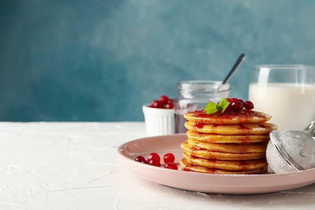 Composición con panqueques con mermelada y arándanos en mesa blanca