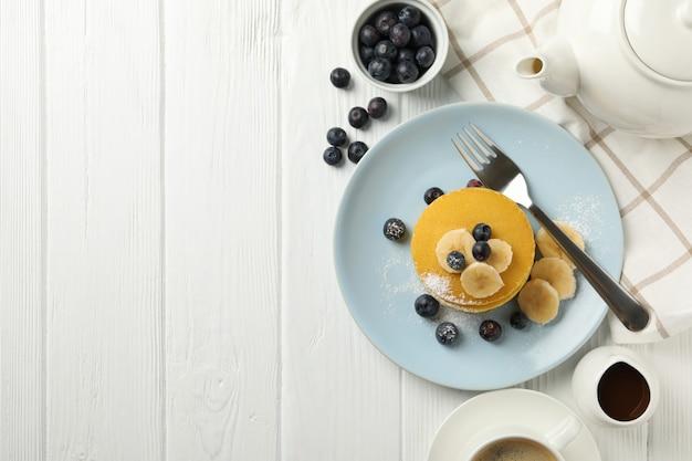 Composición con panqueques, plátano y arándanos en el espacio de madera. desayuno dulce