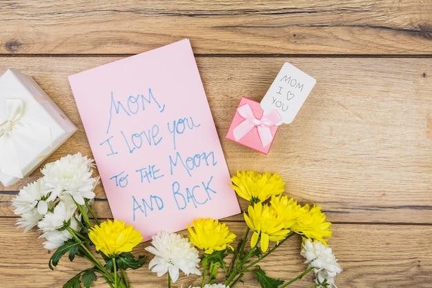 Composición de papel con palabras cerca de flores y regalos.
