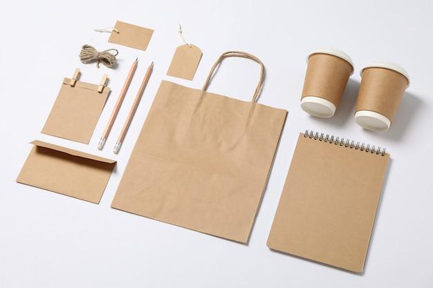 Composición con papelería en blanco, vasos de papel y bolsa sobre fondo blanco.