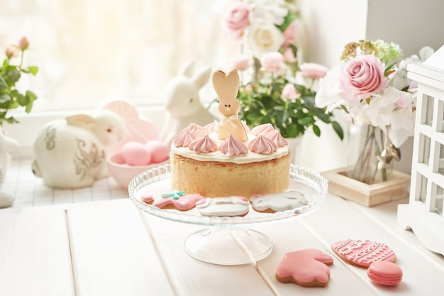 Composición de pascua con dulce pastel con glaseado de fresa, conejitos de cerámica, huevos rosados y rosas
