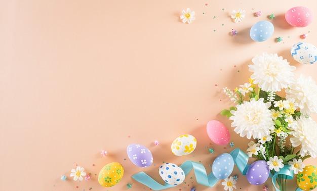 Composición de pascua feliz con coloridos huevos de pascua y flores sobre superficie pastel