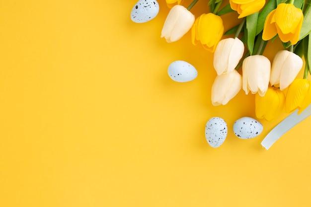 Composición de pascua hecha con tulipanes y huevos pascuales sobre fondo amarillo con espacio de copia
